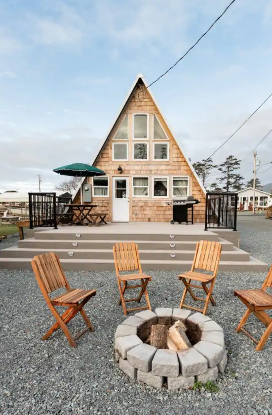 An A-frame cabin on the beach that has a large front patio and a fire pit with wooden folding chairs around it