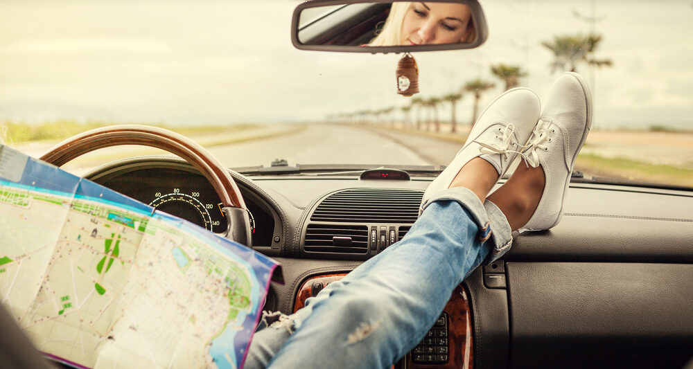 Girl with feet on dashboard of a car in an article about road trip questions