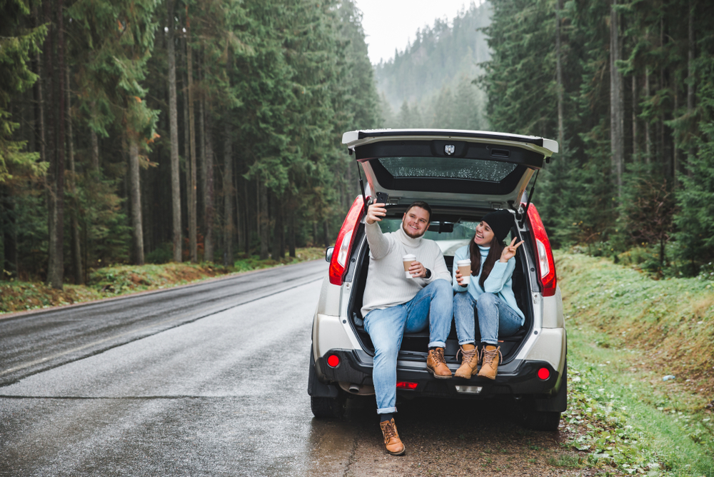 A couple in the back of a car in an article about road trip questions for couples