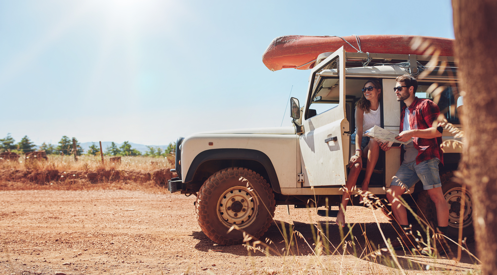 A young couple near a jeep in an article about deep road trip questions
