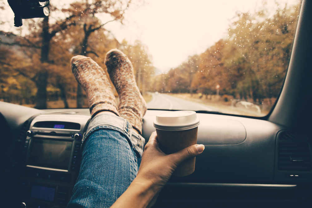 An article about general road trip questions. Picture is a girl with her feet on the dashboard.