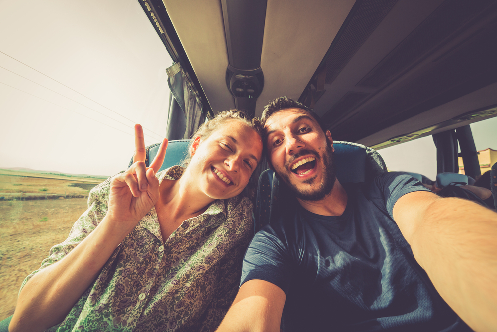 An article about travel road trip questions, picture is two young people on a bus