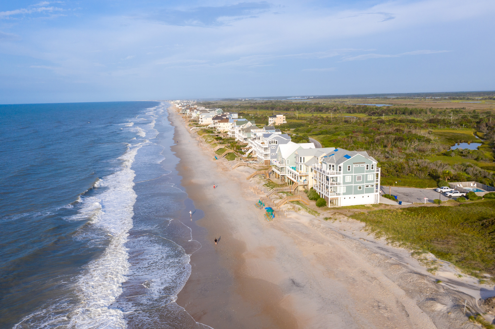 An aerial image looking down the shore line where there are large beach homes on Topsail Beach North Carolina