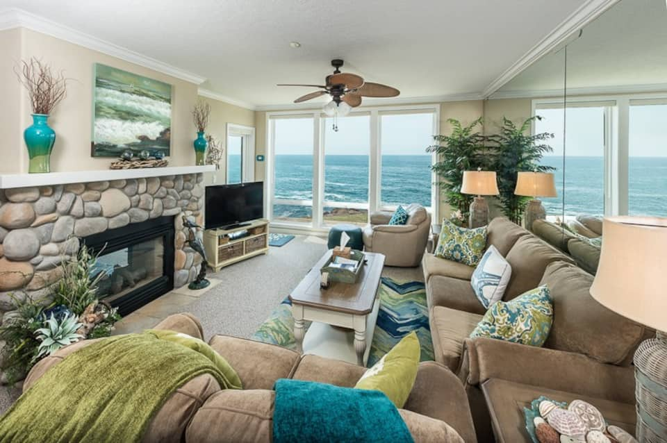 The living area of a condo that has floor to ceiling windows that look out onto the ocean