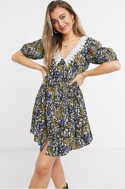 A woman wearing a mini smock dress that is black floral with white, blue, and yellow flowers. It also has v-neck with a crochet peter pan collar.