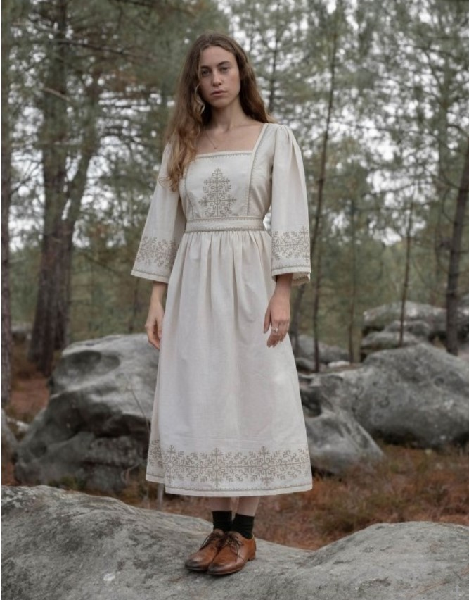 A woman dressed in a white cotton dress with cream embroidery, long sleeves, and midi length hem, standing on a rock in the woods
