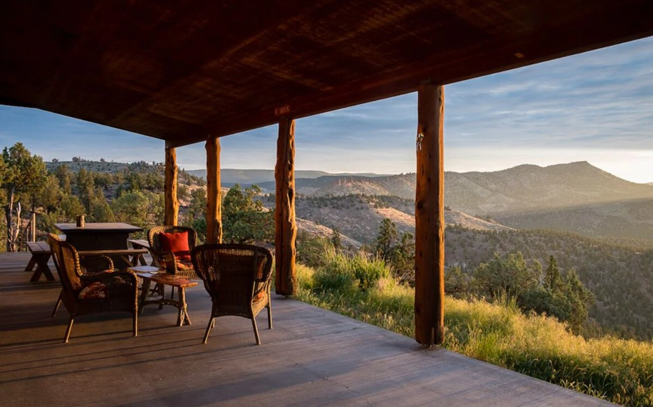 The front porch of a large cabin in Central Oregon that has views of Oregon's highest desert at sunset