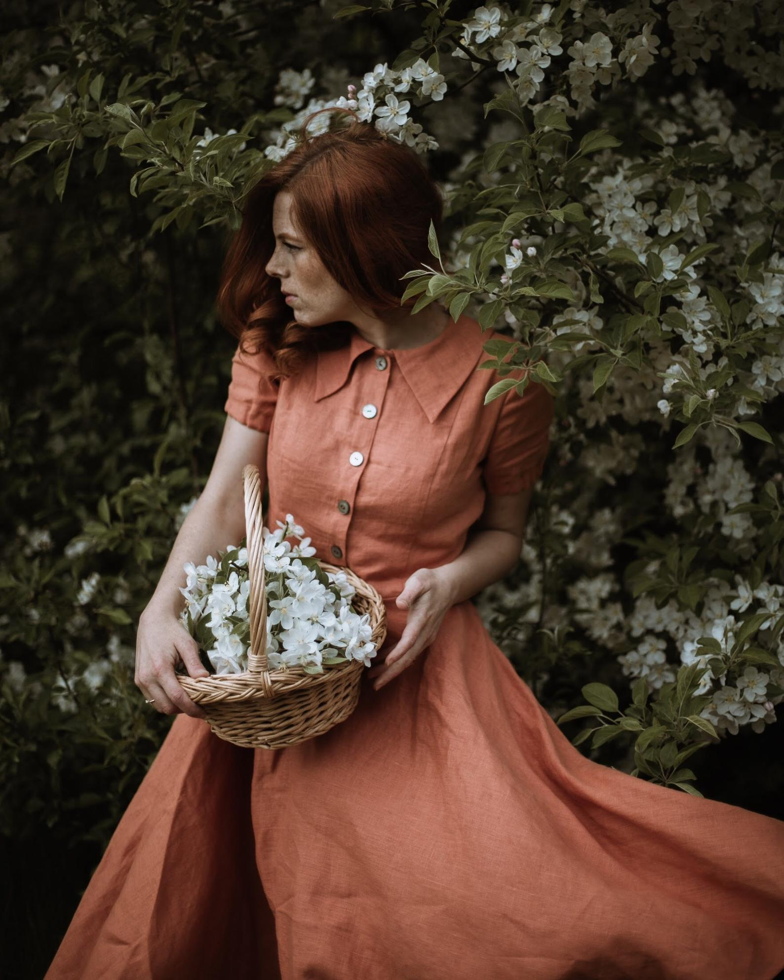 A woman standing against a floral bush wearing a rust colored linen dress with a pointed peter pan collar, buttons down the front, and short puffy sleeves, holding a basket of flowers a perfect cottagecore dress