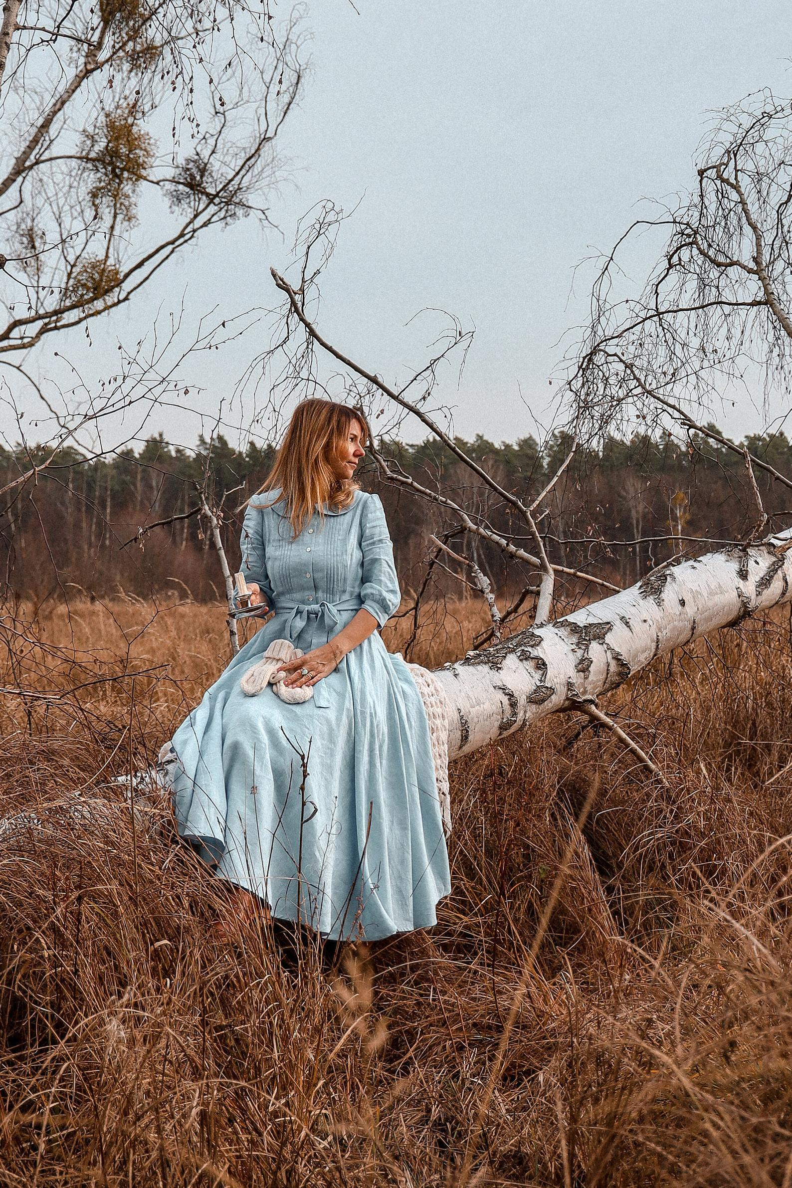 A woman wear an icy blue dress with a full skirt, 3/4 length sleeves, and a peter pan collar sitting on an overturned Burch tree best cottagecore dresses