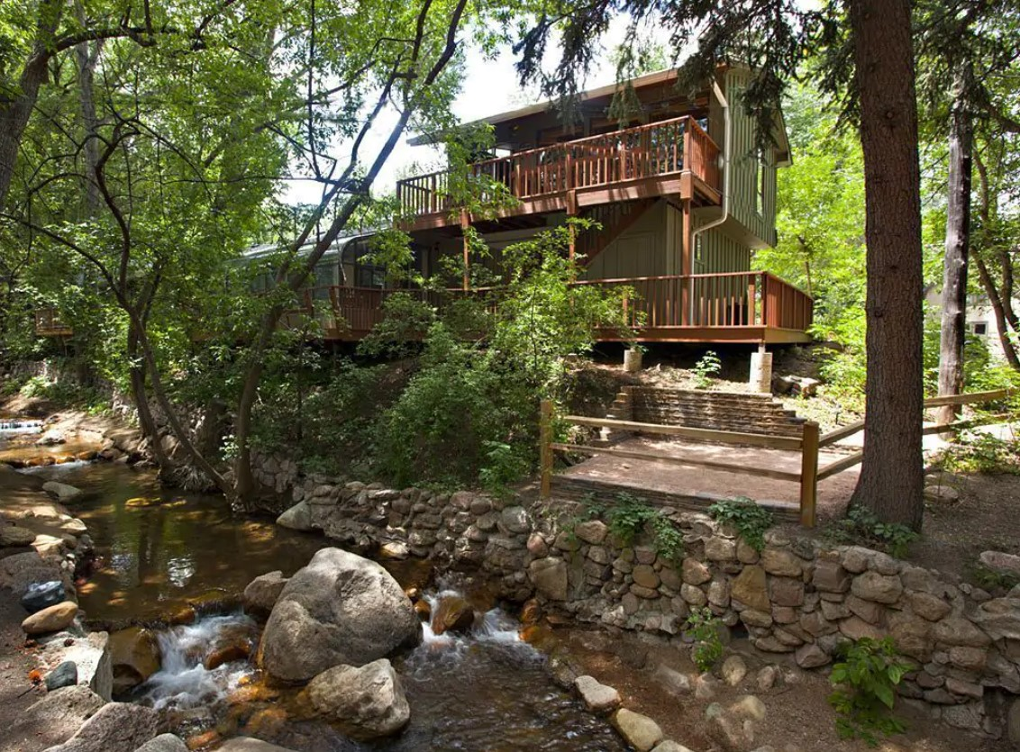 A bungalow style house hidden amongst the trees with a small creek in the backyard