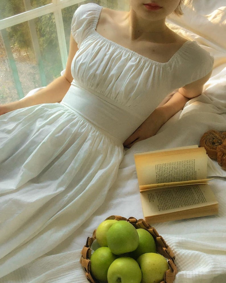 A woman laying down wearing a white cotton dress with a book and a bowl of apples nearby