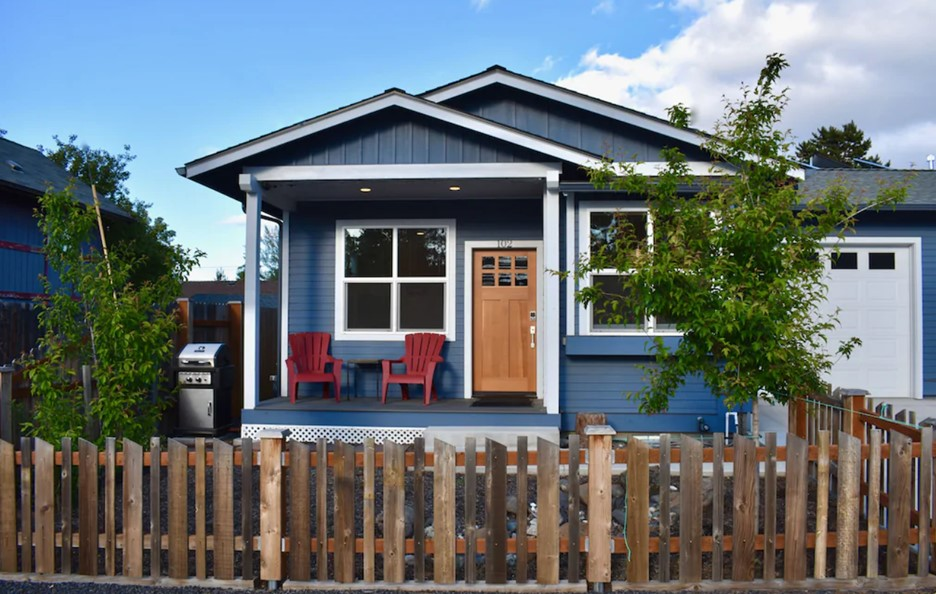 The exterior of a charming cottage in Bend that is painted dark blue, has a small private porch, and a natural wood front door.