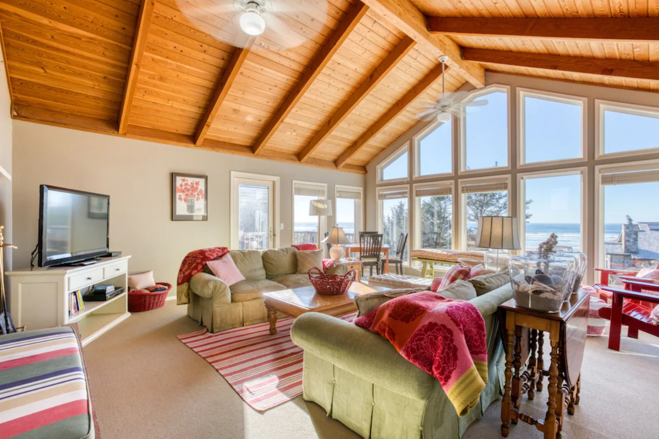 The interior of a large beach house in Oregon with couches, chairs and floor to ceiling windows with views of the ocean