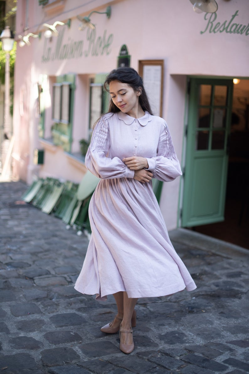 A woman in a dusty rose pink cottagecore dress with long sleeves, a scalloped peter pan collar, and buttons up the front of the chest on a cobblestone street