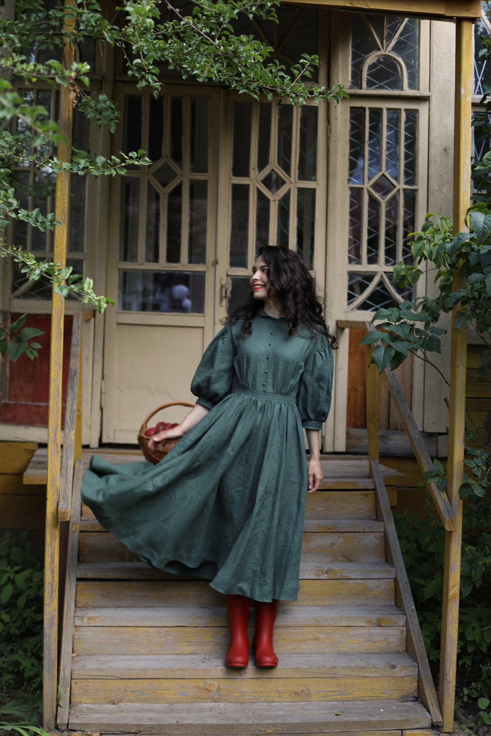 A woman standing on steps in a dark green linen dress with puffy sleeves, buttons down the front, and dark red rainboots.