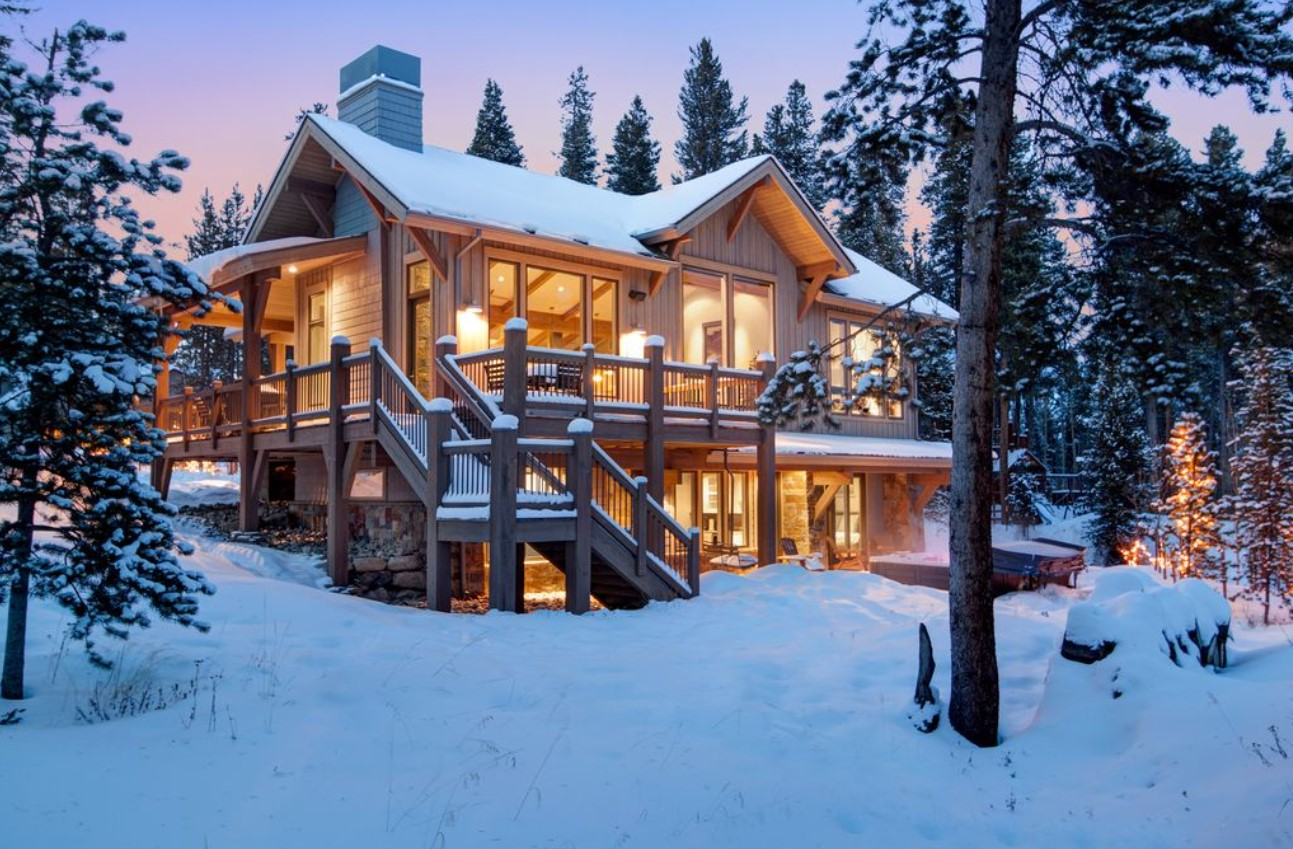 A large luxury villa in the mountains at twilight, covered in snow, and all lit up form the inside.