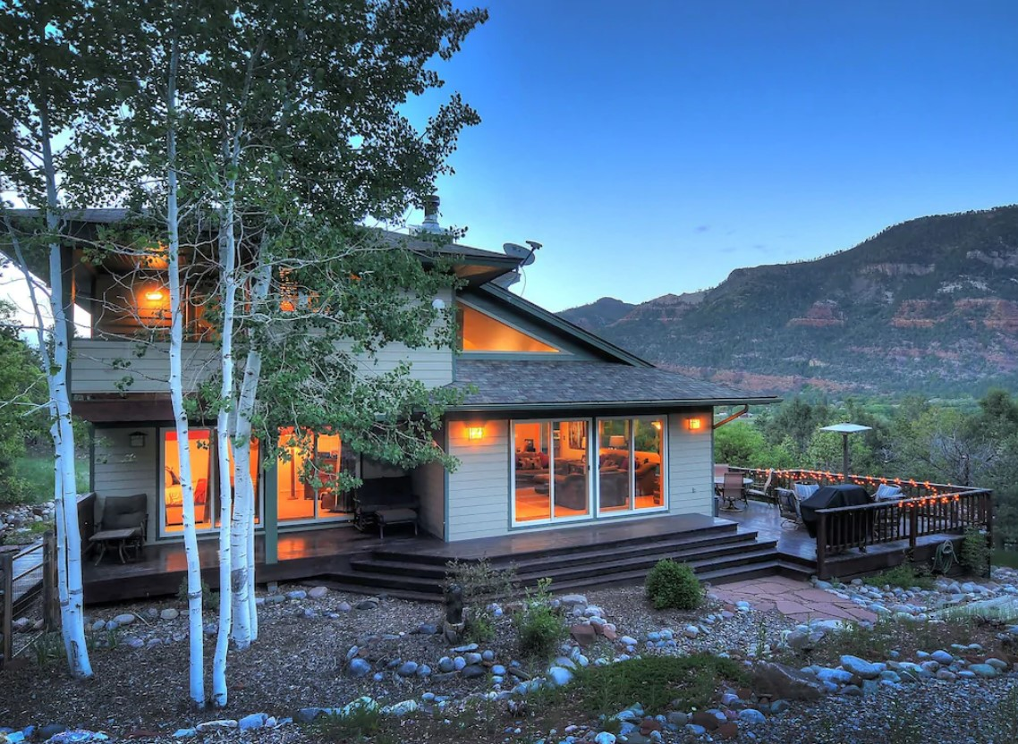 A large mountain home with a modern design with red cliffs in the distance at twilight
