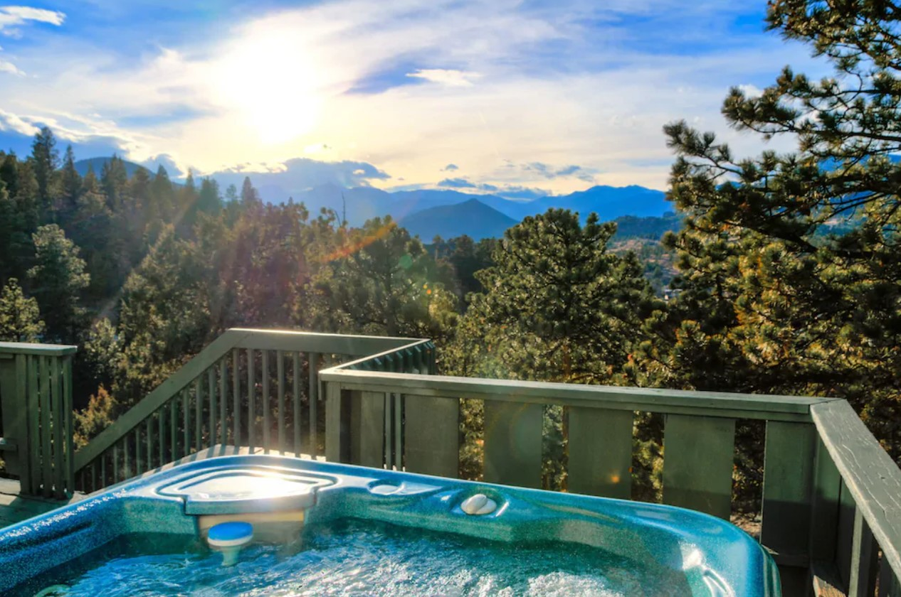 The edge of a hot tub on a deck with views looking out onto the Continental Divide at sunset a great VRBO in Colorado