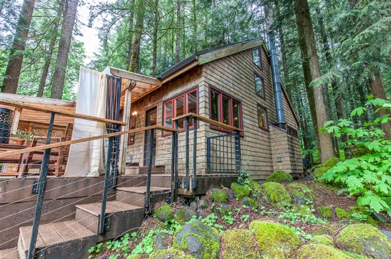 The exterior of a wood shingle cabin in the middle of the woods surrounded by lush greenery with a large deck