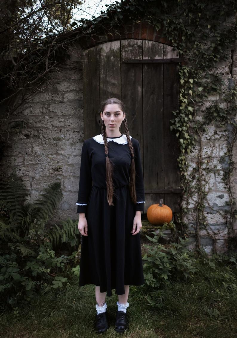 A woman standing in a stone courtyard with greenery around her wearing a black linen dress with a white peter pan collar and lace on the wrists of the long sleeves with a pumpkin behind her best cottagecore dresses