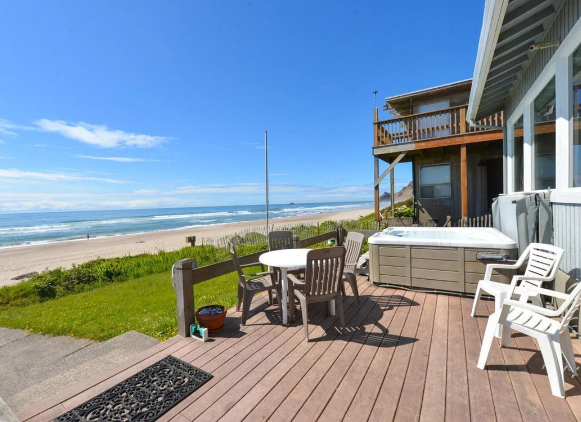 The view of the beach from the private deck at a VRBO in Oregon on a sunny day