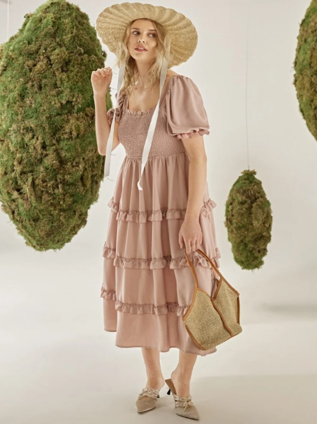 A woman wearing a dusty pink ruffled dress, a sun hat, and a boho purse in a space with topiaries around her
