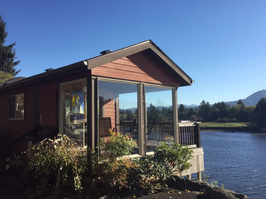 A cottage with a large sunroom and deck over looking a river in Oregon on a sunny day