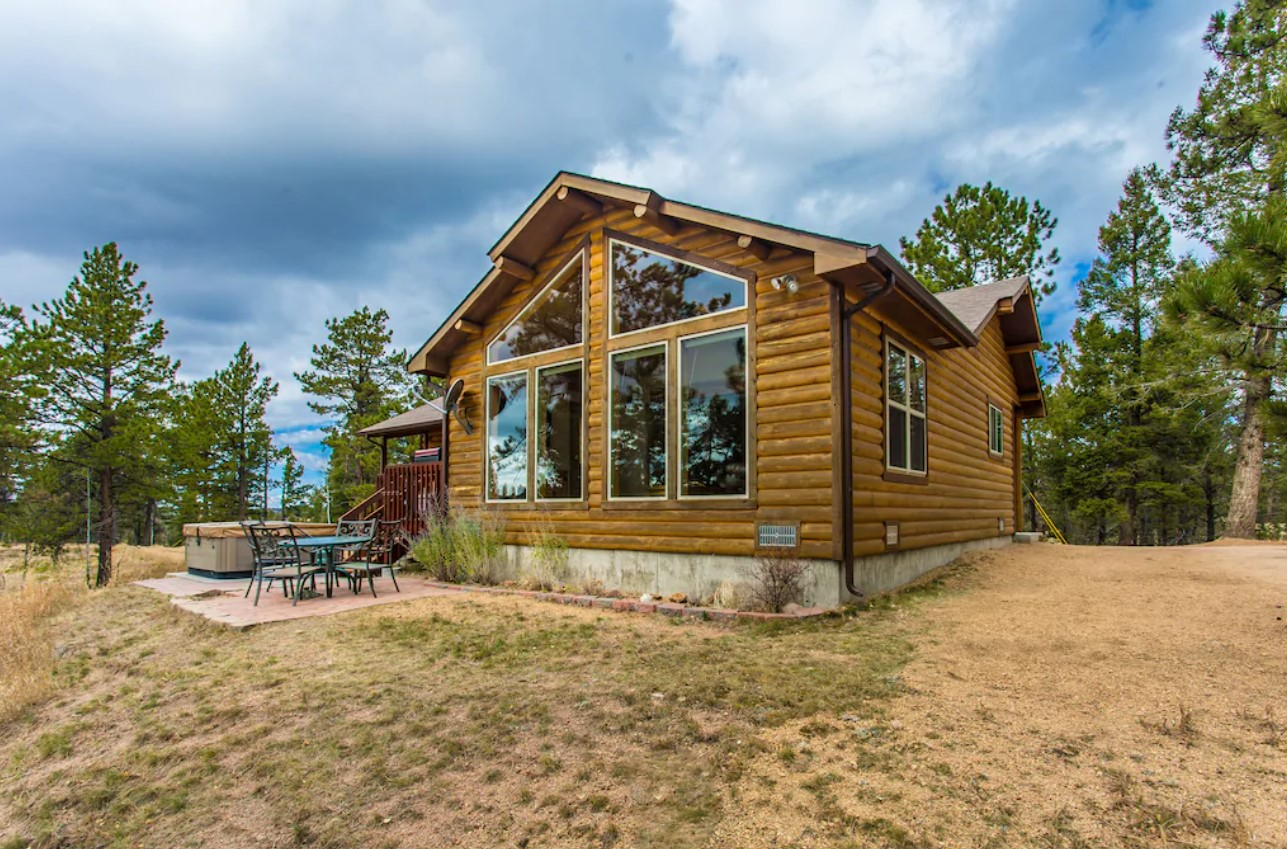 A modern log cabin with plenty of windows, a nice patio, and a hot tub, on a cloudy day