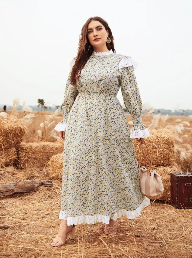 A woman standing in hay wearing a floral maxi dress with lace trim, long sleeves, and a high lace collar