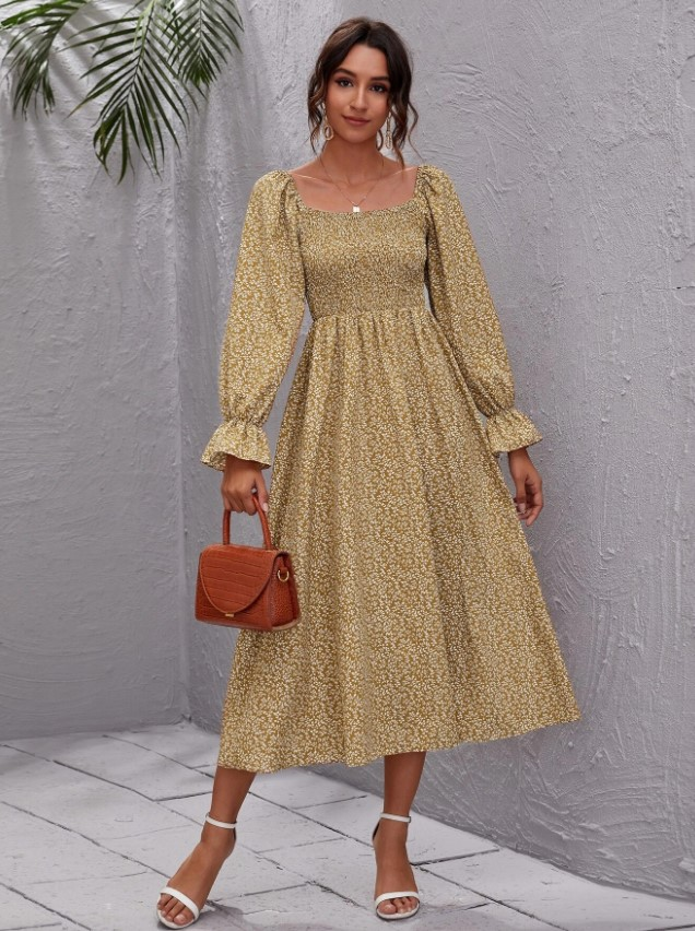 A woman in a long sleeved dark yello maxi floral cottagecore dress