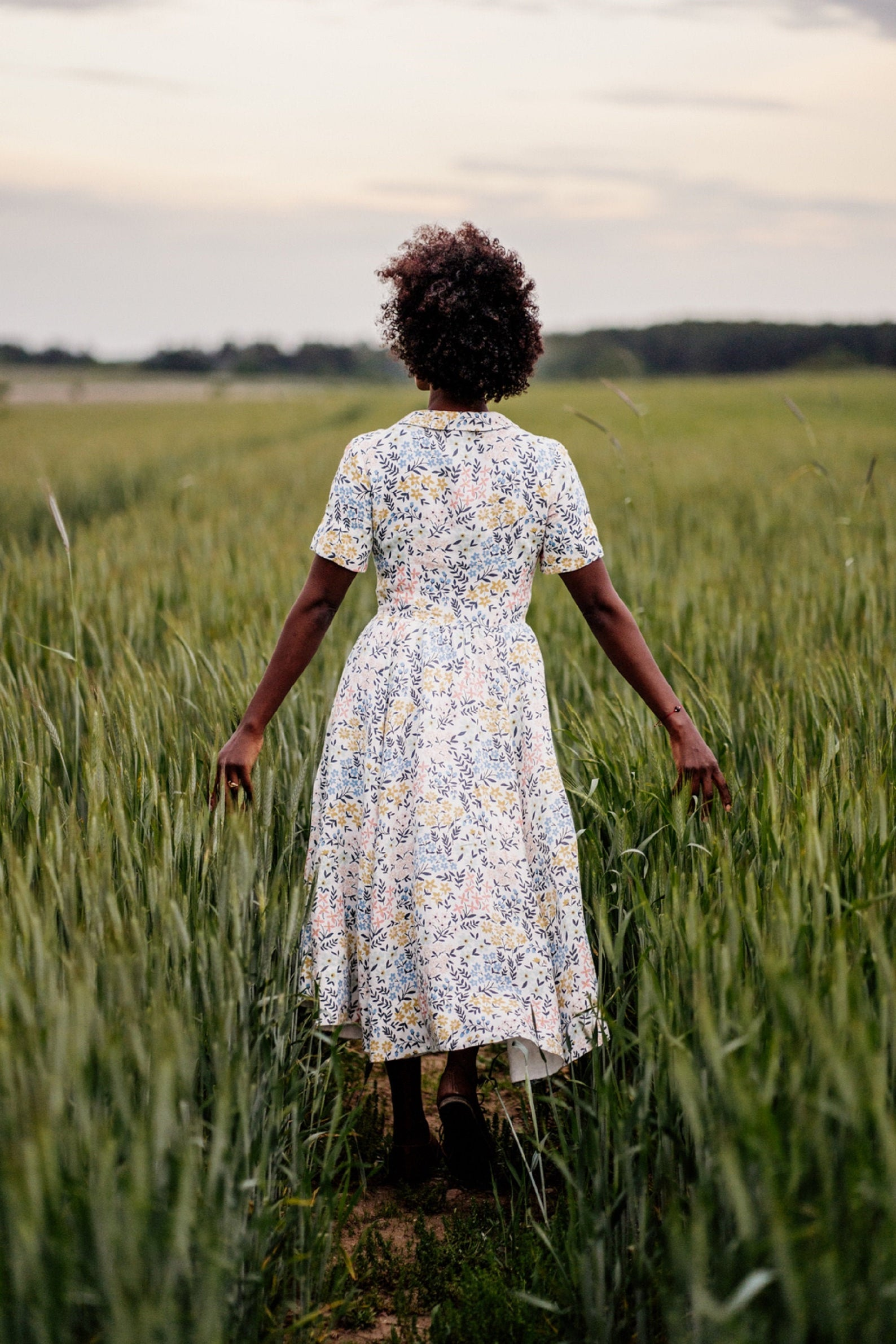 A woman walking in a grassy meadow with her arms stretched out wearing a midi length floral linen dress with short sleeves and a peter pan collar