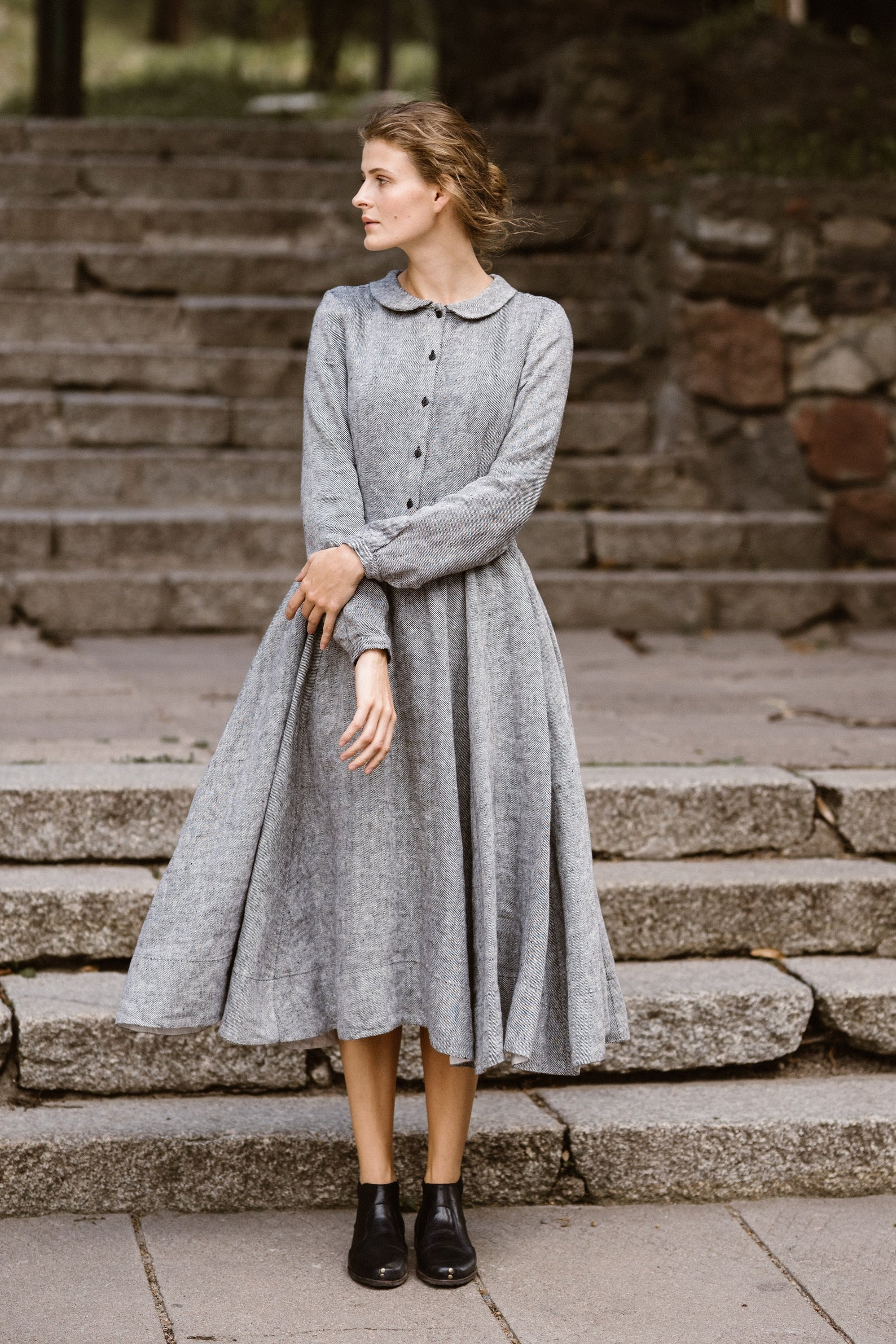 A woman standing on stone steps wearing a grey linen dress with long sleeves, buttons down the chest, and a peter pan collar best cottagecore dresses