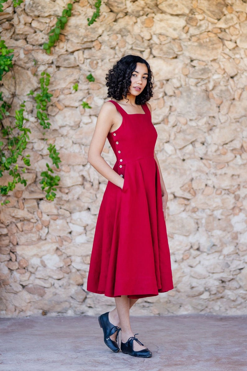 A woman standing in front of a stone wall wearing a red linen dress with buttons on the side and tank top sleeves and pockets
