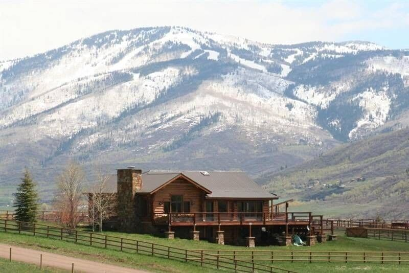 A large log home on a green field with the Rocky Mountains directly in the distance