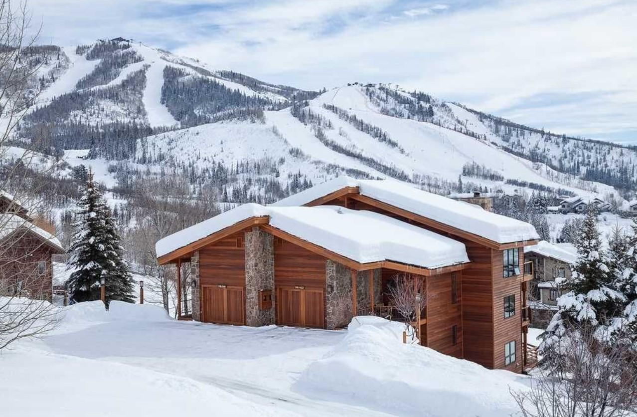 A villa on the side of a hill covered in snow with pretty views of the mountains