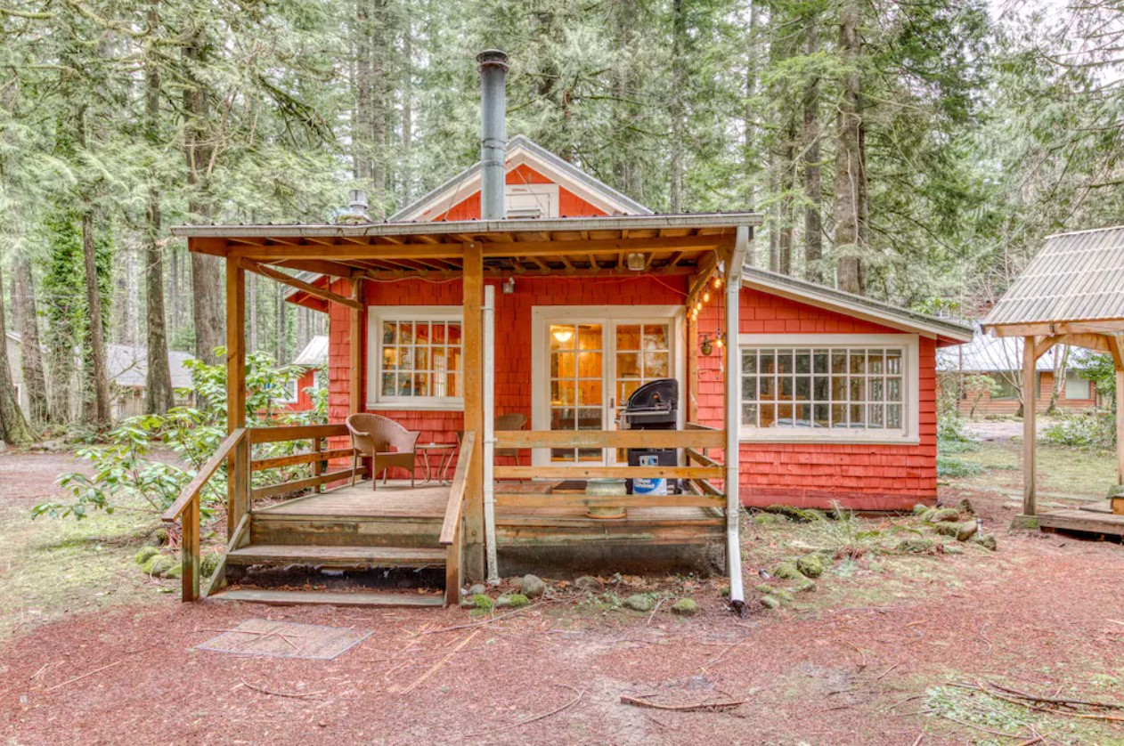 A red cedar shingled single level cabin in the woods of Oregon with plenty of windows