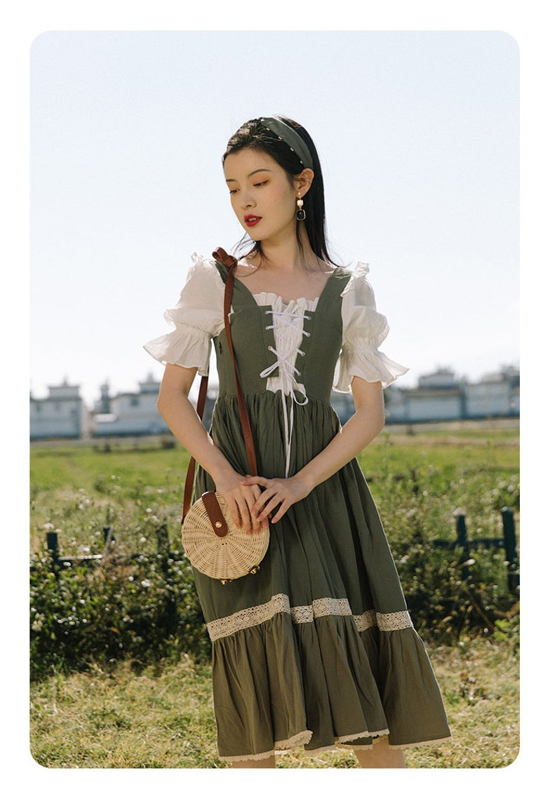 A woman in a green an cream dress that is similar to a Bavarian dress with a lace up corset front, a full skirt, and 3/4 length sleeves