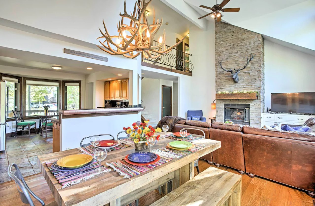 The interior of a upscale mountain home with a large couch, and dining room, and large fireplace VRBO in Colorado