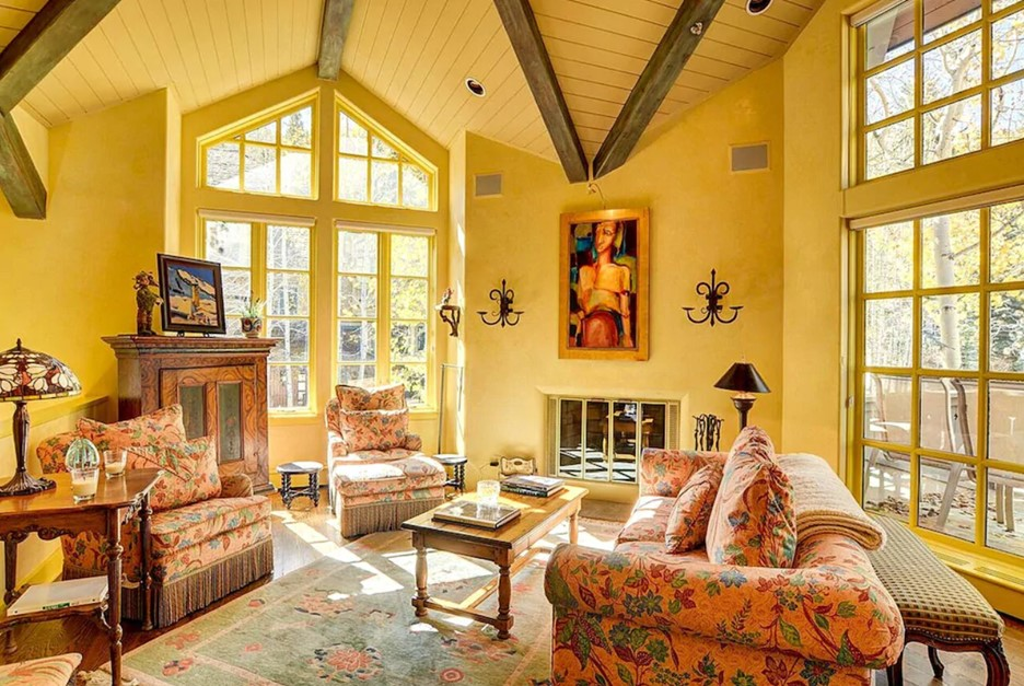 A living area painted a creamy yellow color with cozy furnishings and large windows letting the sun in