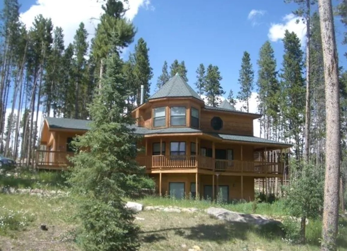 A large log cabin with three levels, a large deck, and a turret, surrounded by trees on a sunny day VRBO in Colorado