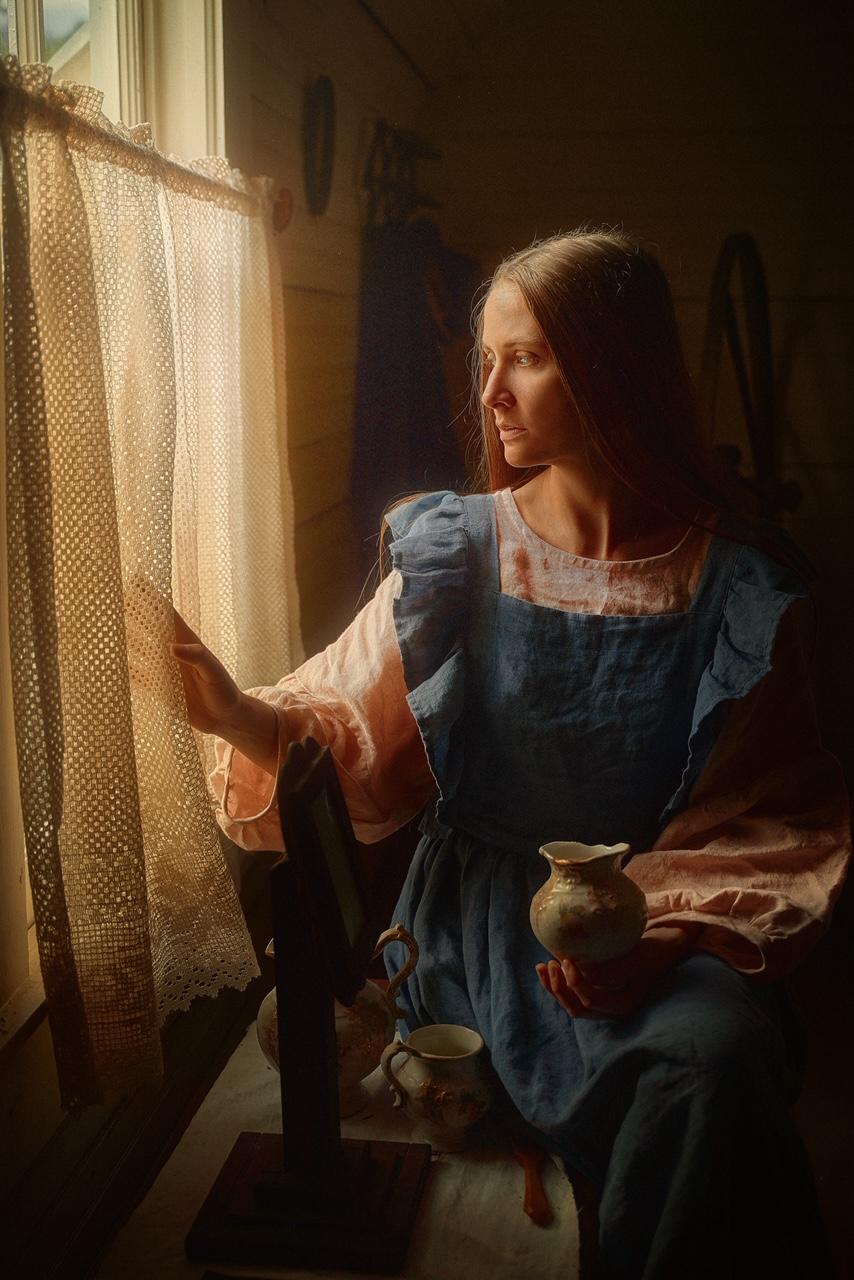 A woman sitting by a window wearing a pink tunic and blue sleeve ruffle dress