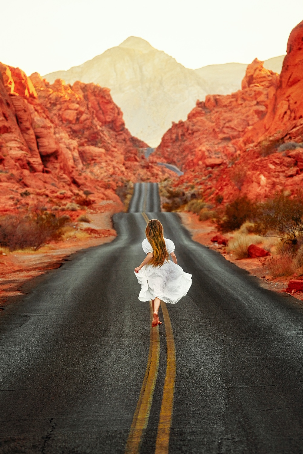 A woman running down a street surrounded by orange and red rock formations wearing a white dress best cottagecore dresses