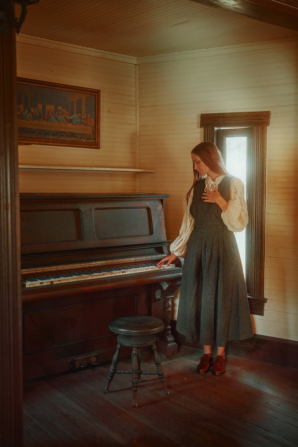 A woman standing by a piano wearing a grey linen dress