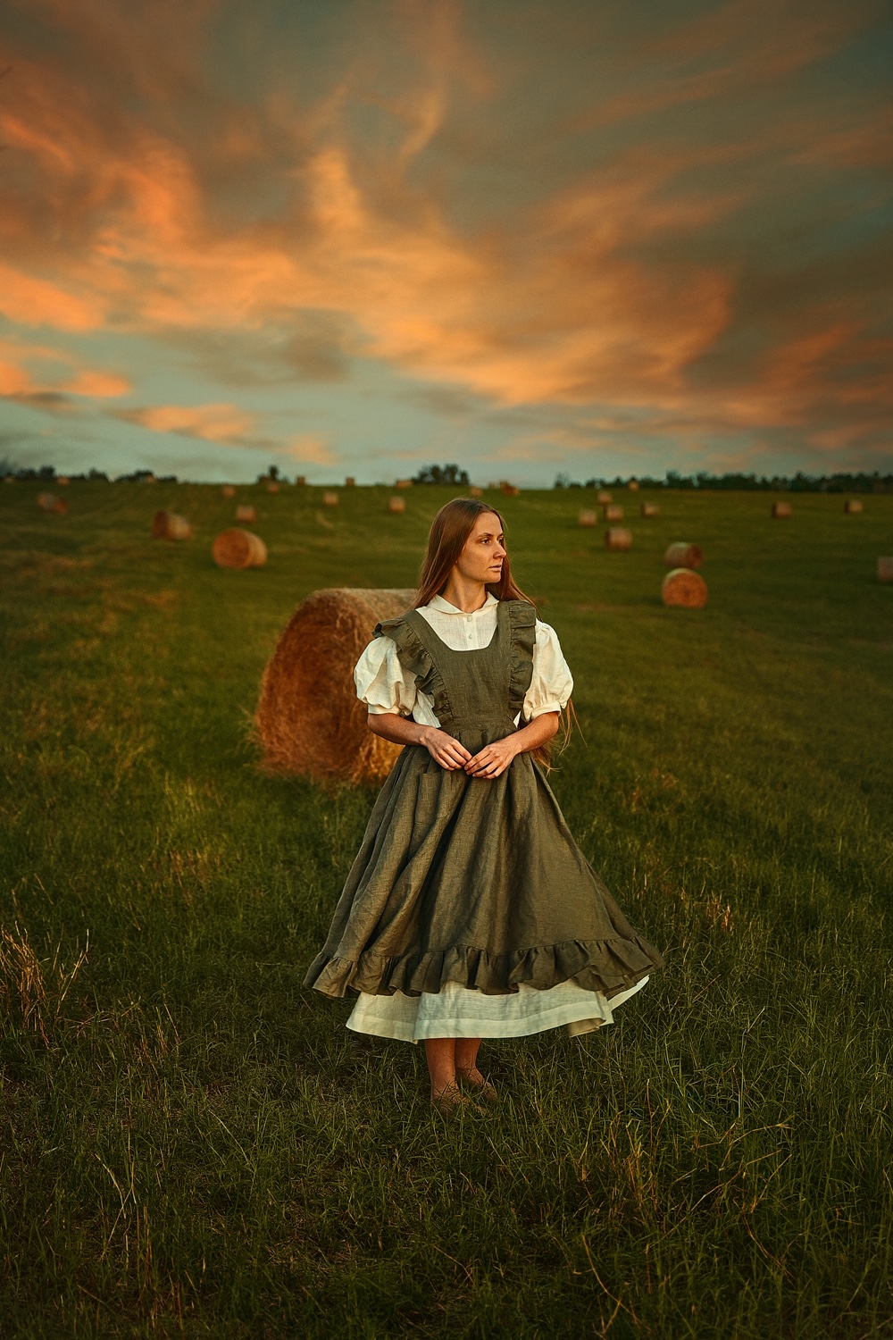 A woman standing in a field of stacked hay wearing a cottagecore dress and pinafore