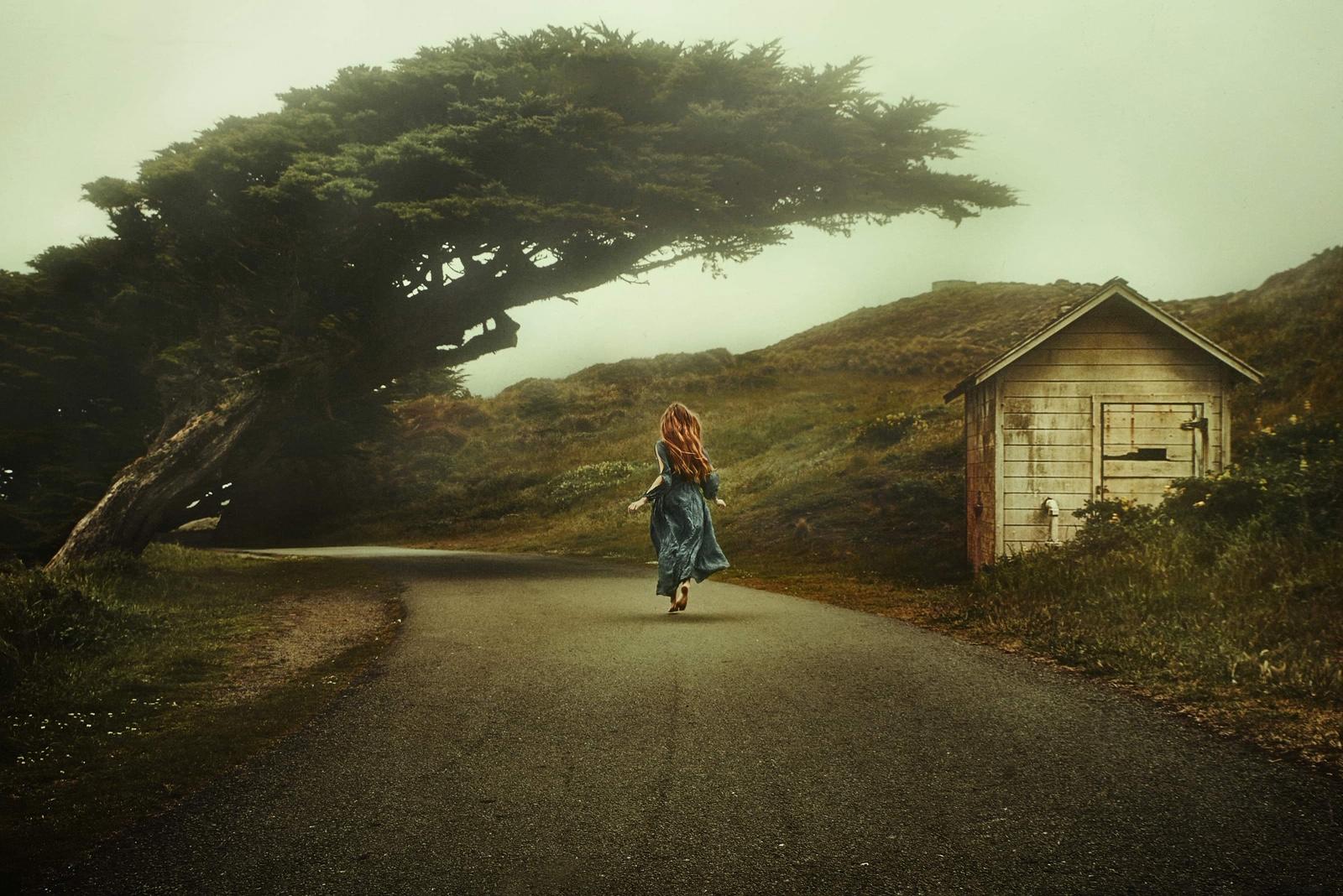 A woman walking away in a dark blue cottagecore dress