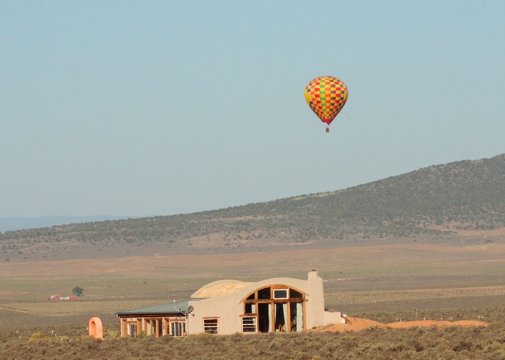 A clay home with large windows and a domed roof line in the desert of New Mexico. There is nothing around it except for a slight hill in the background. Floating near the home in the sky is a hot air balloon with red, green, orange, blue, and purple checked fabric.