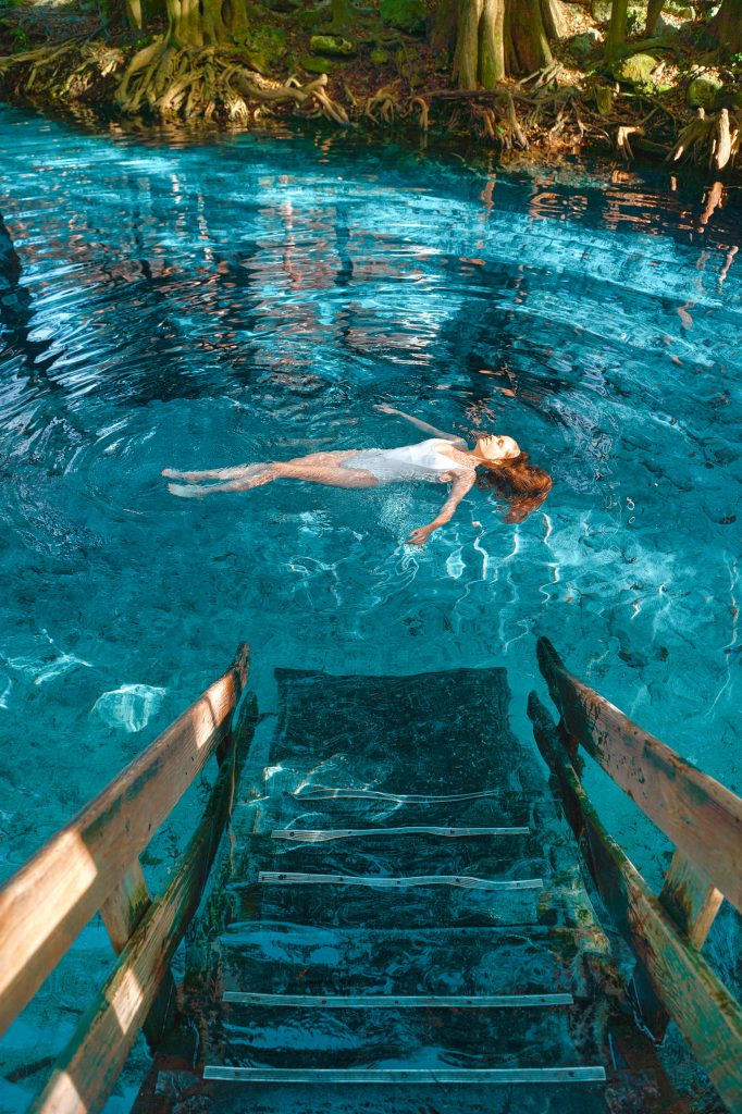 Girl swimming at Ginnie Springs, a great place to see on a Florida road trip or weekend getaway on the East Coast.