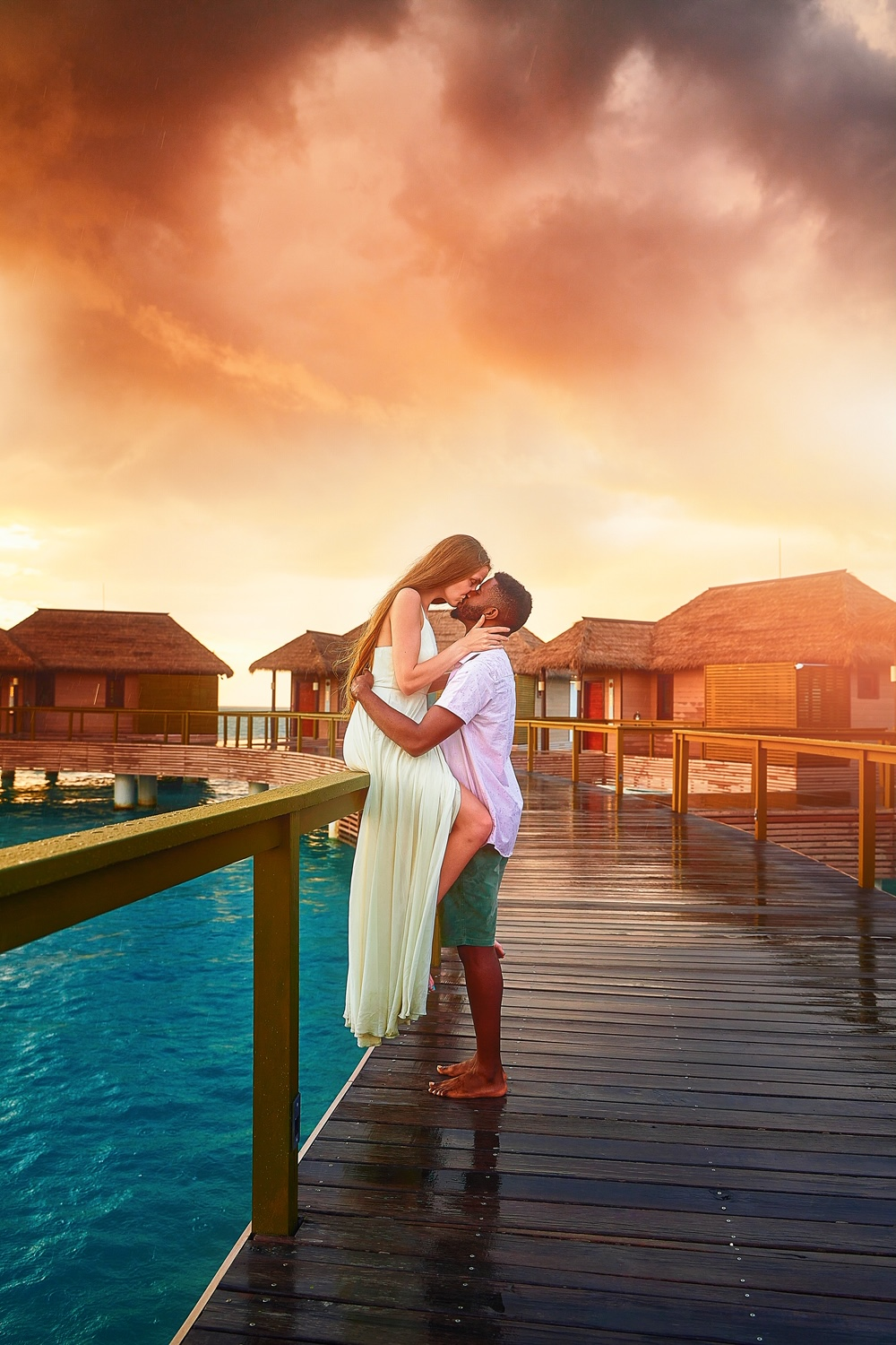 A couple kissing on a dock surrounded by overwater bungalows in Jamaica at sunset