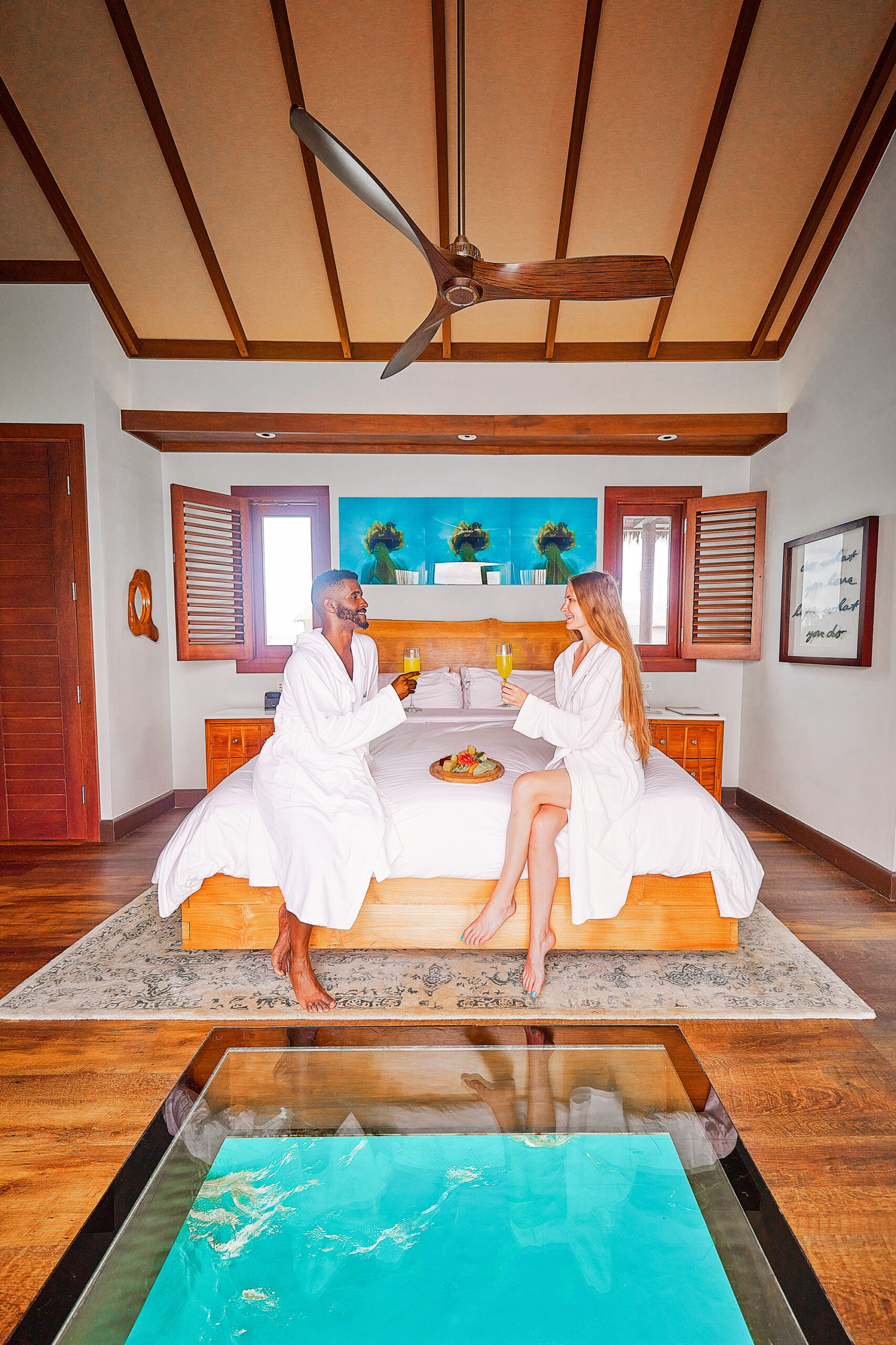 A couple sitting on a bed enjoying mimosas and fruit in their robes with an window to the ocean near their feet