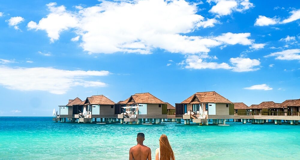 A couple standing in the ocean looking at overwater bungalows in Jamaica